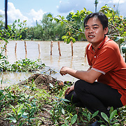 CAPTION: Nhi is the Vice Chairman of the People's Committee of An Binh Ward; here, he indicates the progress that has been made so far in constructing erosion barriers on this part of the riverbank. LOCATION: An Binh Ward, Can Tho, Vietnam. INDIVIDUAL(S) PHOTOGRAPHED: Huynh Ha Nhi.