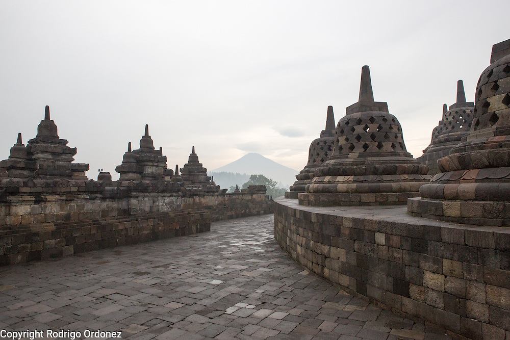 View of the top level of Borobudur temple and the volcanic landscape, in Central Java, Indonesia. The top circular platform of the monument (right) has 72 perforated stupas with seated Buddha statues inside.