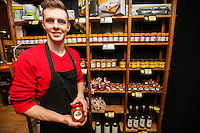 Portrait of smiling salesperson holding jar in supermarket