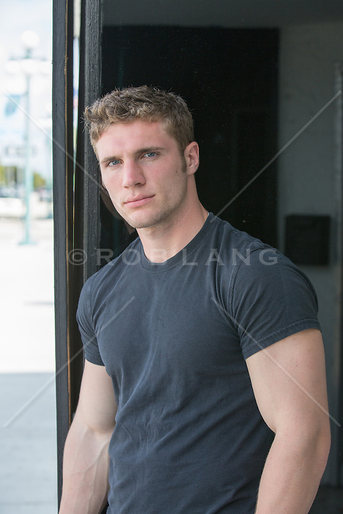 rugged handsome man in a black tee shirt  outdoors