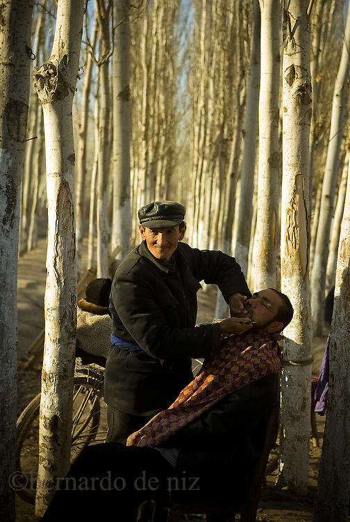 "An Uyghur barber, shave a client at the Opel´s Bazaar, 100 kilometers from Kashgar, In Xinjiang Autonomus region in China, March, 2009. Photographer: Bernardo De Niz..The Uighurs are an ethnically Turkic Muslim people who have lived in what is now known as the Xinjiang Uighur Autonomous Region (XUAR) for over 4,000 years. Known as Eastern Turkestan for hundreds of years,.Xinjiang is located along the famous ""Silk Road"", beyond the Great Wall, the natural boundary of China. Islam.entered the region in the middle of the tenth century and has flourished among the Uighurs ever since."