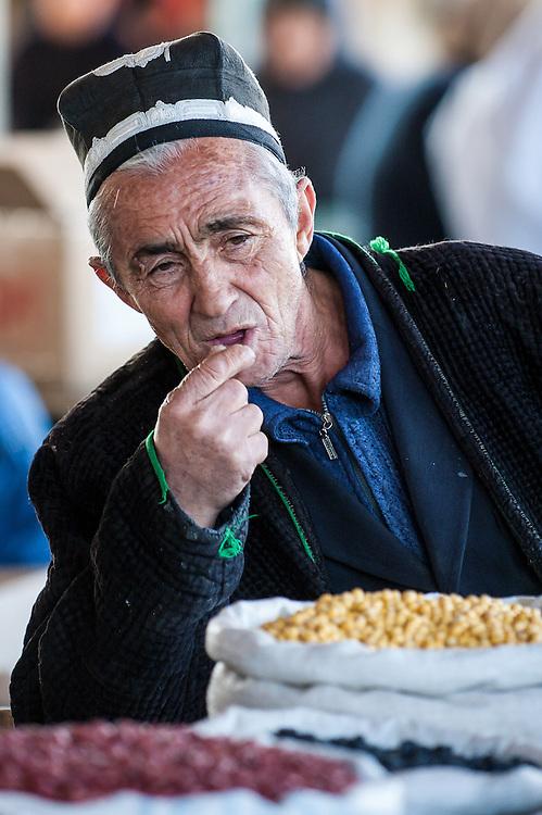Portrait of an old Tajik man eating his produce in a market in western Tajikistan
