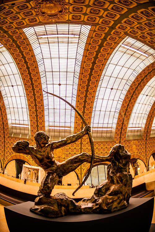 "Gilded bronze statue ""Hercules the Archer"" aka ""Hercules Killing the Birds of Lake Stymphalis"" by Emile-Antoine Bourdelle, Musee d""Orsay,  a museum in Paris, France, on the Left Bank of the Seine. It is housed in the former Gare d'Orsay, a Beaux-Arts railway station built between 1898 and 1900."