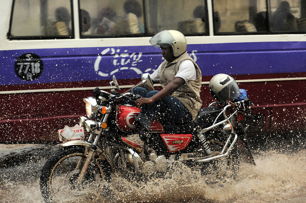 DAR ES SALAAM, TANZANIA -  13-12-03  -  A motorcyclist drives down flooded United Nations Road during a rain storm in Dar es Salaam, Tanzania on December 3, 2013. Photo by Daniel Hayduk
