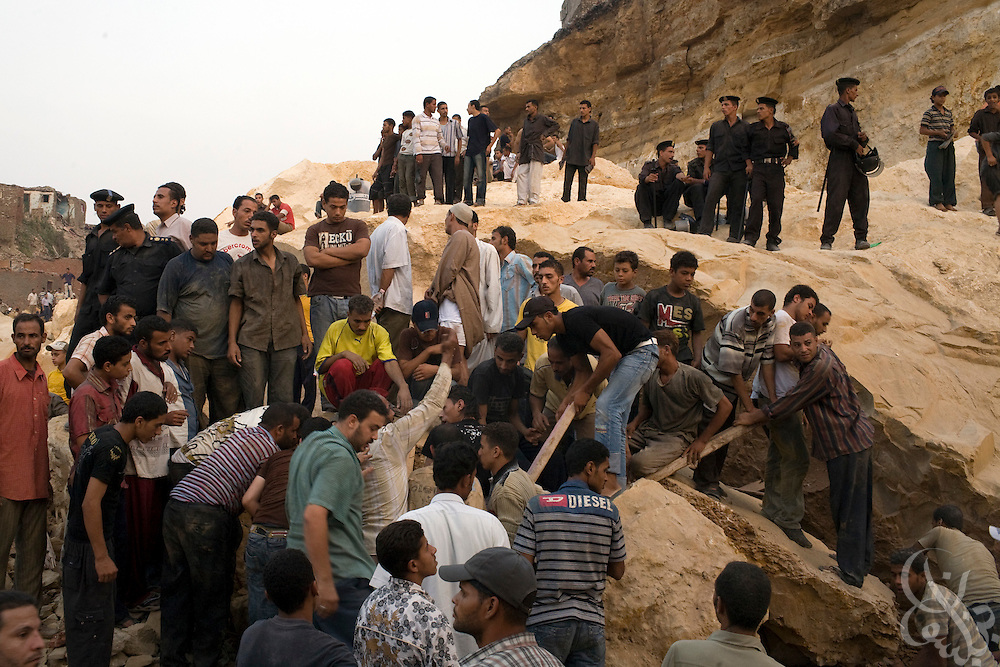 Egyptian residents of the Manshiyet Nasr shantytown try to move a giant boulder left by a rock slide that killed at least 64 and buried perhaps hundreds more Saturday September 06, 2008 on the eastern edge of Cairo, Egypt. Residents have complained that the government appears to be doing little to reach possible survivors, and have clashed with police at the site of the disaster.