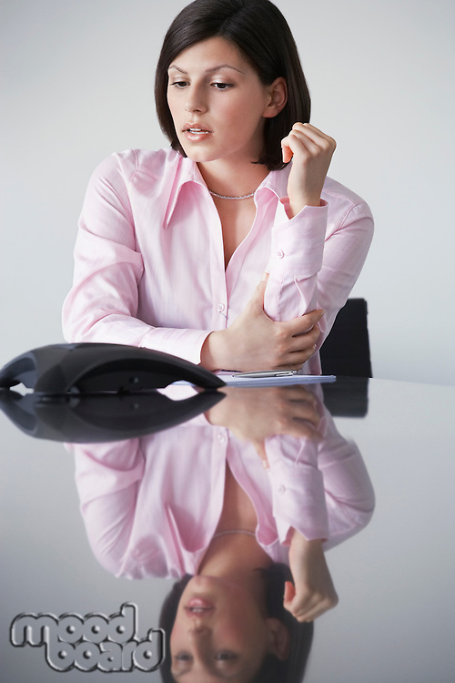 Business woman waiting beside telephone at conference table