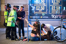 © Licensed to London News Pictures . 11/09/2016 . Manchester , UK . A woman reaches out her hand towards a police officer as another is tended to on the ground , on Withy Grove . Revellers out in Manchester City Centre . Photo credit : Joel Goodman/LNP