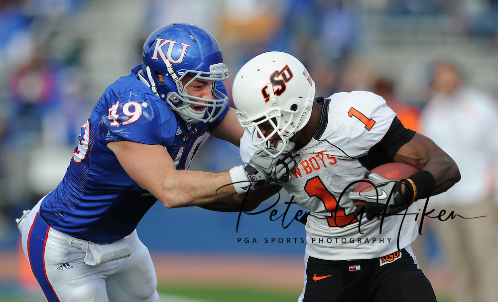 Linebacker Drew Dudley #49  of the Kansas Jayhawks grabs the facemask of running back Joseph Randle #1 of the Oklahoma State Cowboys during the third quarter at Memorial Stadium in Lawrence, Kansas.  Oklahoma State beat Kansas 48-14...