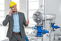 Young male manager in hard hat using cell phone by machinery in industry