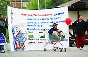 """Rostock   June 2, 2007   ..Mehr als 50000 Menschen demonstrieren in Rostock gegen den G8-Gipfel in Heiligendamm, gegen Kapitalismus, Militarismus, Krieg und gegen die Politik der G8-Staaten. Hier: Ein Mann ruht sich in einem Einkaufswagen vor einem Plakat mit der Aufschrift """"Aktiver Widerstand gegen Bushs new War"""" aus...More than 50000 people take part in a demonstration in the german city of rostock against the G8-summit in Heiligendamm, against capitalism, militarism, war and the politics of the G8 states. Here: A man takes a rest sitting in a shopping cart in front of a banner wich reads """"active resistance against Bushs new war""""...20070602g8 ...[Inhaltsveraendernde Manipulation des Fotos nur nach ausdruecklicher Genehmigung des Fotografen. Vereinbarungen ueber Abtretung von Persoenlichkeitsrechten/Model Release der abgebildeten Person/Personen liegen nicht vor.]"""