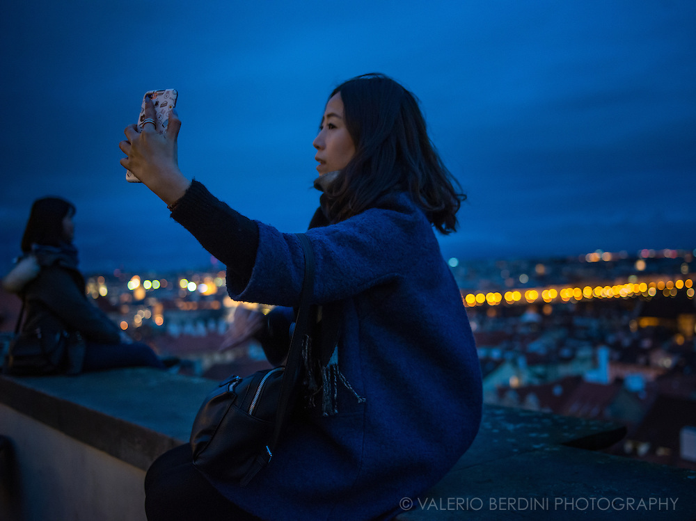 An asian girl poses for a selfie overlooking Old Prague seen from Prague Castle