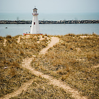 Photo of the lighthouse in New Buffalo Michigan with a sandy grass trail and jetty rock breakwall in the background.