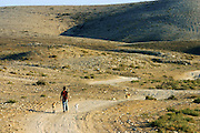 A Bedouin man is walking near the unrecognised village of Wadi el Na'am, pop. 4000, close to Beer Sheva, the capital of the Negev, a large deserted area in the south of Israel.  Wadi el Na'am is located near a large industrial site, Ramat Hovav, and has no infrastructure or electric energy. Water is provided only via storage tanks. It has no health services as the only clinic is deemed illegal and bound to be demolished, as the rest of the structures in the area. Numbering around 200.000 in Israel, the Bedouins constitute the native ethnic group of these areas, they farm, grow wheat, olives and live in complete self sufficiency. Many of them were in these lands long before the Israeli State was created and their traditional lifestyle is now threatened by subtle Governmental policies. The seven Bedouin towns already built are all between the 10 more impoverished towns in Israel. ..