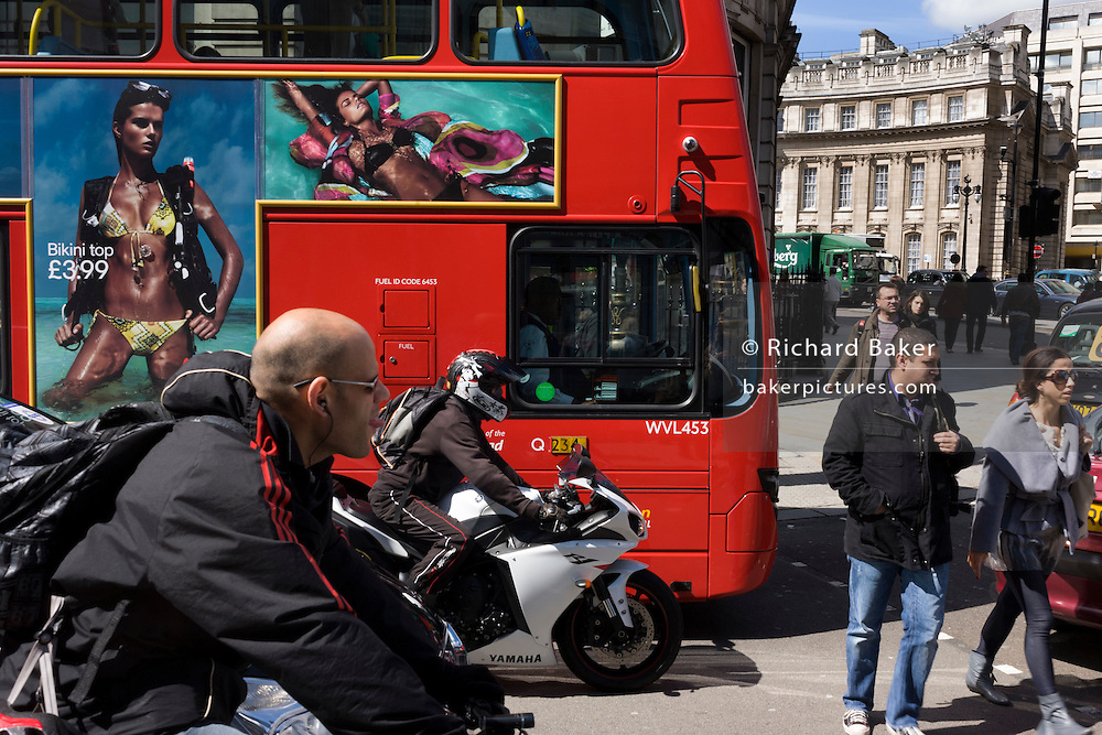 Bikini-wearing model on a bus ad and crossing pedestrians in a busy London street.