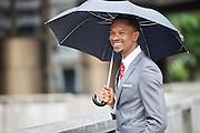 Happy African American businessman holding umbrella