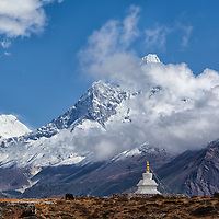 "Ama Dablam (6856m), partially hidden by clouds, and a yak grazing beside a chorten as we continue our descend from ""Everest View Hotel"" to Khumjung."