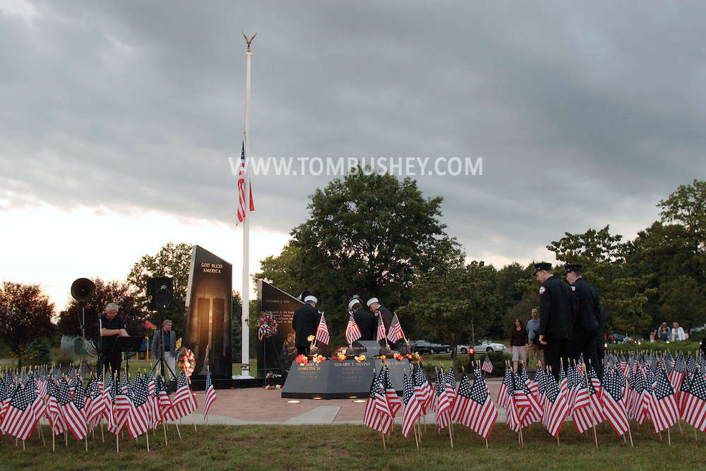 Washingtonville, N.Y. - People, including firefighters in dress uniforms, gather at the Washingtonville 5 Firefighters World Trade Center Memorial before a candlelight service on Sept. 11, 2008. The Memorial was built in honor of five FDNY firefighters from Washingtonville and the many others who lost their lives on September 11, 2001 in the World Trade Center terrorist attack.