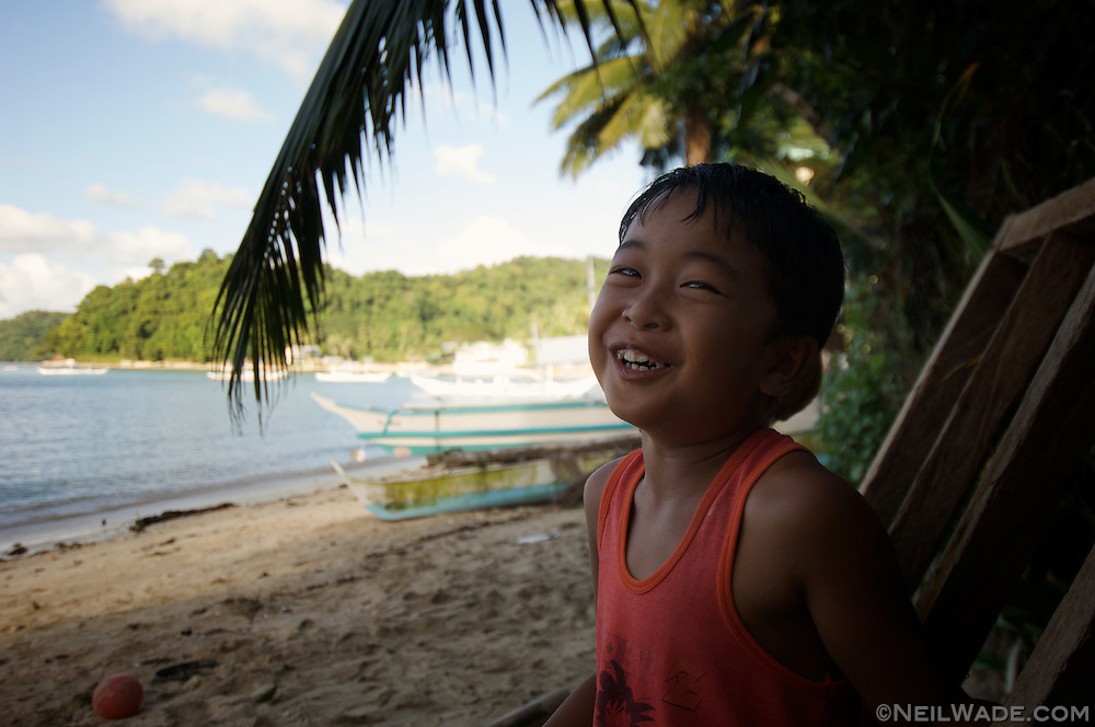 A Filipino child smiles to the camera on the beach in El Nido Town, Palawan, Philippines.