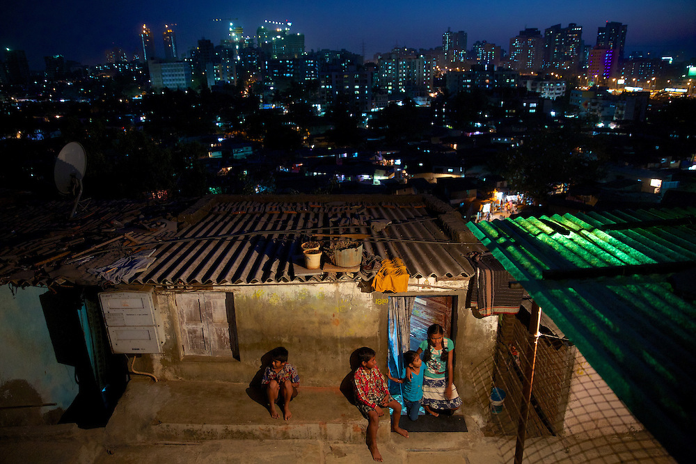Children playing in urban slums at night, in Mumbai. Every day hundreds of millions of people in India wake up at dawn and work hard until sunset to find their way out of poverty. Many of these people cannot access clean water and electricity, nor pay school fees for their children or see a doctor when they are sick. Their basic needs have been largely unmet, neither by public services nor by the market that doesn't consider them as potential customers. Access to health care services in India by low-income people is limited due to the poor supply from the public service, especially in remote areas such as slums.
