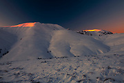 The top of the mountain covered in deep snow at sunrise