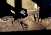 A guard is dwarfed by the giant stone statue of Ramses II in Memphis.