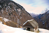 Ticino, Southern Switzerland.  Wood and stone hut on the snowy slopes with view down the valley.