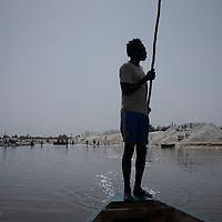 Un piroguier dirige sa barque vers les recruteurs de sel, cette activité fait partie de attractions touristiques du Lac Rose.
