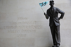 London, UK. 11 October, 2019. An Extinction Rebellion flag is placed on a statue of George Orwell outside the BBC's New Broadcasting House on the fifth day of International Rebellion protests by Extinction Rebellion. Activists were demanding that the broadcaster 'tell the truth' regarding the climate emergency.