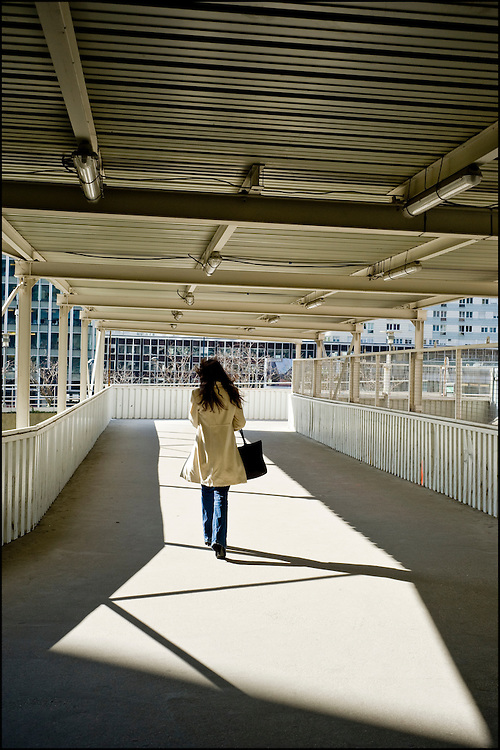 A woman is heading to her office in early afternoon after a lunch break in La Défense, outskirt of Paris.