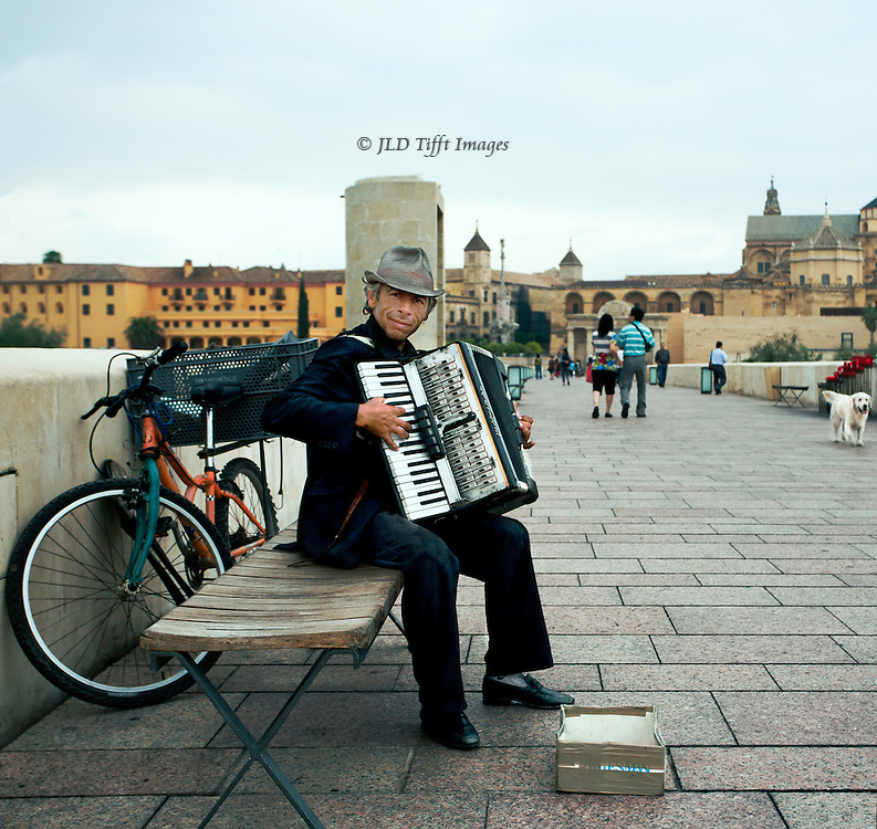 Gypsy accordionist performs on the pedestrian bridge into the old city of Cordoba, Spain.  Pedestrians and a white dog pass by.