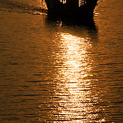 A golden sunset silhouettes a boat on the Perfume River in Hue, Vietnam.