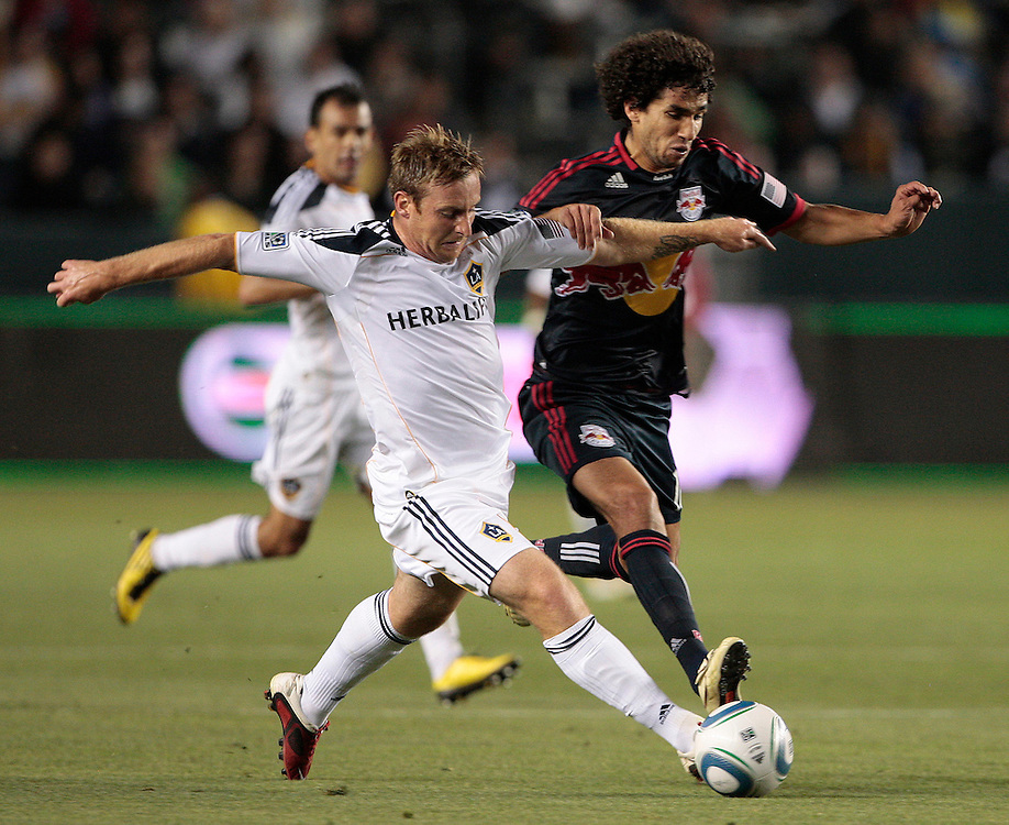 Los Angeles Galaxy midfielder Chris Birchall, left, of England and New York Red Bulls midfielder Mehdi Ballouchy, right, of Morocco vie for the ball during the second half of a MLS soccer match, Saturday, May 7, 2011, in Carson, Calif. The game ended in a 1-1 tie. (AP Photo/Jason Redmond)