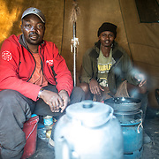 Two camp cooks prepare food in the kitchen tent at Mweka Camp on Mt Kilimanjaro.