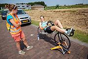 Lieke de Cock praat met haar coach. Op een weg in Delft worden de eerste meters afgelegd met de nieuwe recordfiets, de VeloX 8. In september wil het Human Power Team Delft en Amsterdam, dat bestaat uit studenten van de TU Delft en de VU Amsterdam, tijdens de World Human Powered Speed Challenge in Nevada een poging doen het wereldrecord snelfietsen voor vrouwen te verbreken met de VeloX 8, een gestroomlijnde ligfiets. Het record is met 121,81 km/h sinds 2010 in handen van de Francaise Barbara Buatois. De Canadees Todd Reichert is de snelste man met 144,17 km/h sinds 2016.<br /> <br /> At a road in Delft the team tests the VeloX 8 for the first time. With the VeloX 8, a special recumbent bike, the Human Power Team Delft and Amsterdam, consisting of students of the TU Delft and the VU Amsterdam, also wants to set a new woman's world record cycling in September at the World Human Powered Speed Challenge in Nevada. The current speed record is 121,81 km/h, set in 2010 by Barbara Buatois. The fastest man is Todd Reichert with 144,17 km/h.