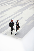 Businessman and businesswoman walking across outdoor plaza elevated view