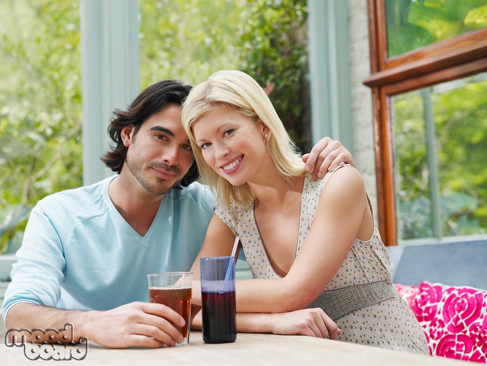 Young couple sitting at verandah table smiling portrait