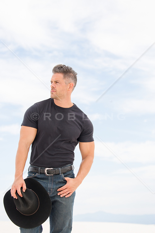 cowboy holding his hat outdoors