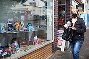 A cat is practising social distance from humans in a shopping window in Stierstadt while a woman with a face mask is passing by.