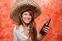 Happy woman in Mexican hat holding beer bottle in restaurant