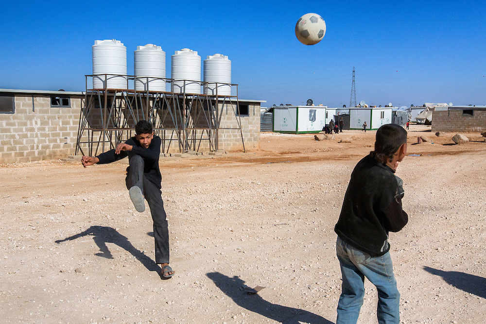 A game of soccer, or futbol, is a regular sight within the camp. Behind the players is one of dozens of makeshift restrooms with water tanks that the camp administration must fill regularly for plumbing. Feb. 8, 2014. Zaatari Camp, Jordan. (Photo by Gabriel Romero/Alexia Foundation ©2014)