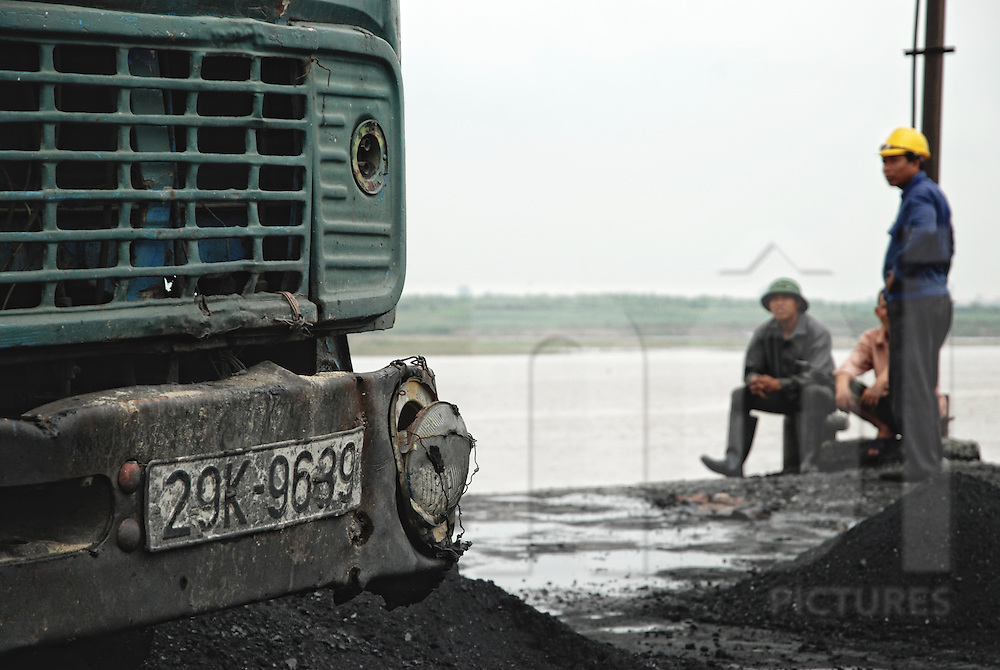 radiator grille of an old truck with workers in background. Shallow depth of field and selective focus on the vehicule while the background is blurred.