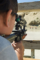 Man aiming rifle at firing range