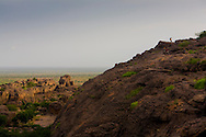 Tourists walking on the Bandiagara Escarpment in the Dogon Country. The Dogon Country is the most visited part of Mali with tourists visiting its tipical  villages that can be located on the cliff, on the sandy plain or in the rocky plateau
