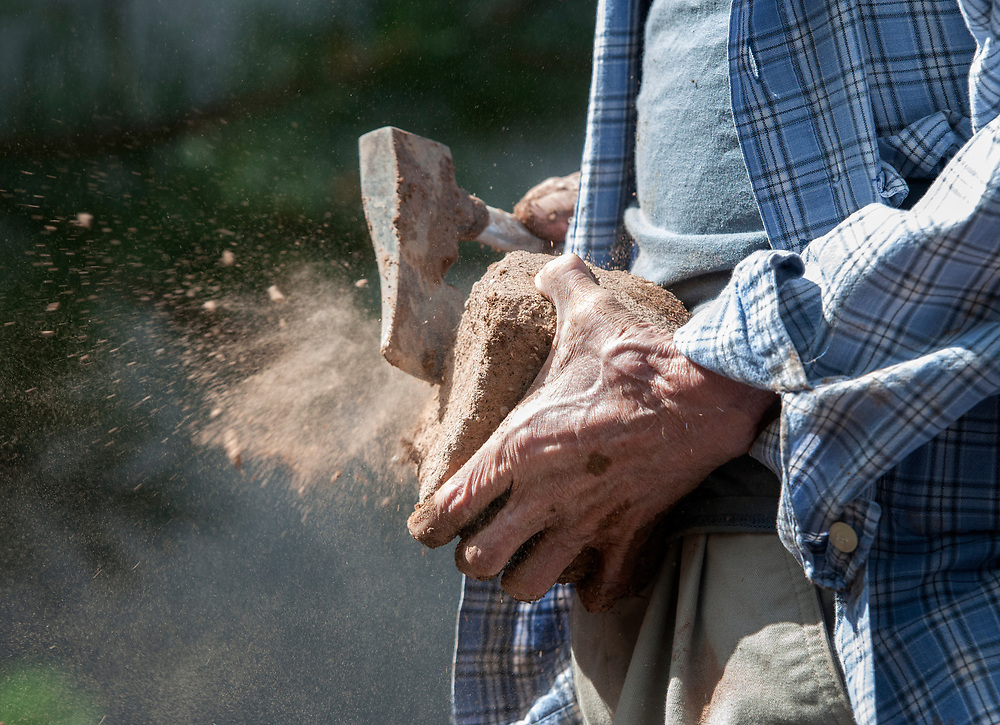 em071917i/jnorth/Felipe Ortega, from La Madera, uses a hatchet to cut down the size of an adobe brick to finish a horno he is helping build in the courtyard of the Palace of the Governor's in Santa Fe, Wednesday July 19, 2017. (Eddie Moore/Albuquerque Journal)