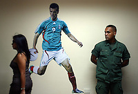 Fussball   International   42. Copa America   Feature           Im Buero fuer Presseakkreditierung sorgt ein Soldat fuer Sicherheit und schaut einer venezolanischen Frau nach. An der Wand haengt ein Poster vom mexikanischen Nationalspieler BORGUETTI.