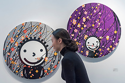 "© Licensed to London News Pictures. 16/01/2018. LONDON, UK. A staff member views ""Breeze silver"" and ""Gentle breeze-violet"" by Korean artist Kisoo Kwon. Preview day of the 30th anniversary of the London Art Fair.  The fair launches the international art calendar with modern and contemporary art from leading galleries around the world and is taking place at the Business Design Centre, Islington from 17 to 21 January 2018.   Photo credit: Stephen Chung/LNP"