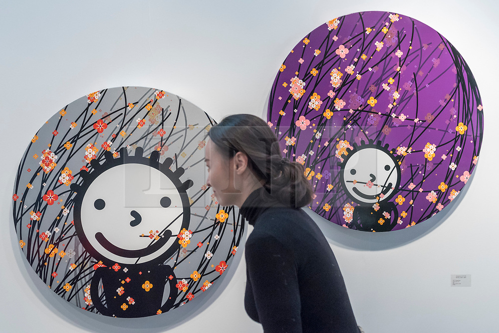 """© Licensed to London News Pictures. 16/01/2018. LONDON, UK. A staff member views """"Breeze silver"""" and """"Gentle breeze-violet"""" by Korean artist Kisoo Kwon. Preview day of the 30th anniversary of the London Art Fair.  The fair launches the international art calendar with modern and contemporary art from leading galleries around the world and is taking place at the Business Design Centre, Islington from 17 to 21 January 2018.   Photo credit: Stephen Chung/LNP"""