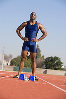 Athlete standing next to starting block, ready to run