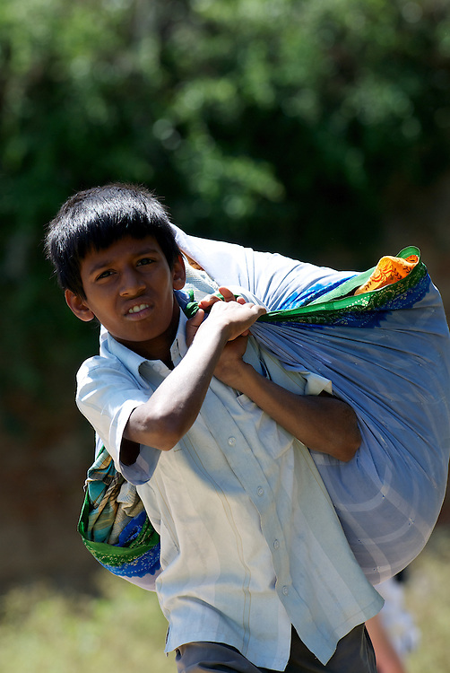 A boy carries washing to the riverside to wash in Mysore, India