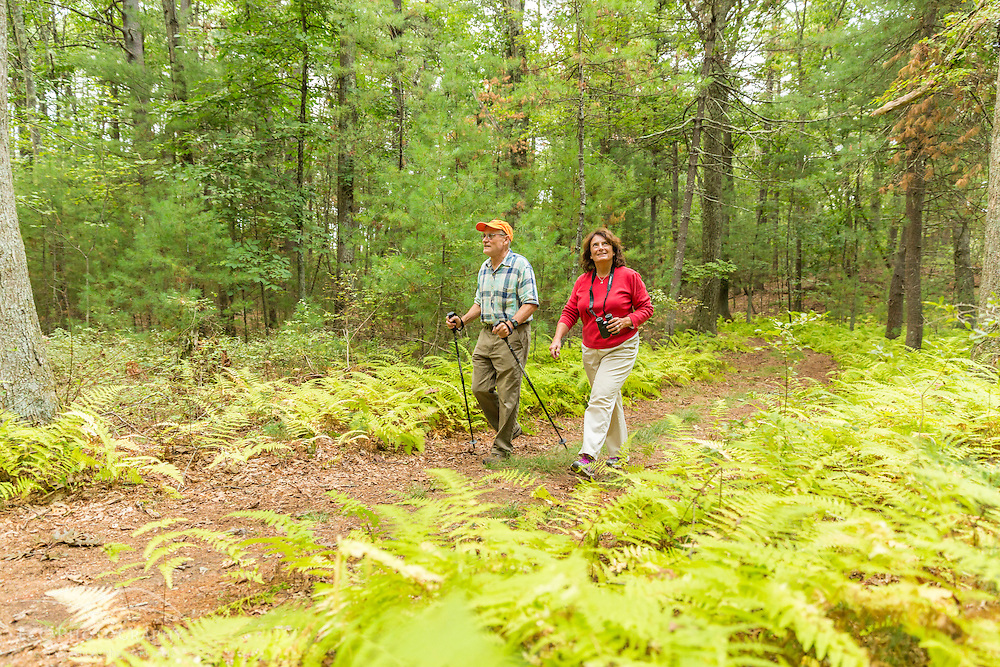 A man and woman hike a woodland trail in Ipswich, Massachusets.